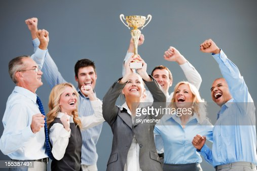 Cheerful group of businesspeople winning the cup with hands up.