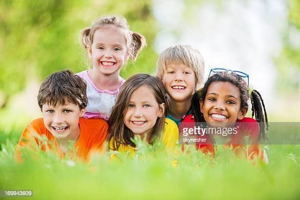 Fröhliche Gruppe von Kindern im park liegen.