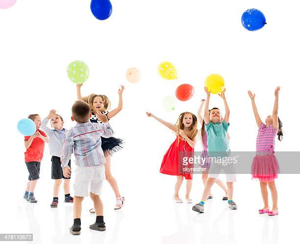 Cheerful group of children playing with balloons.