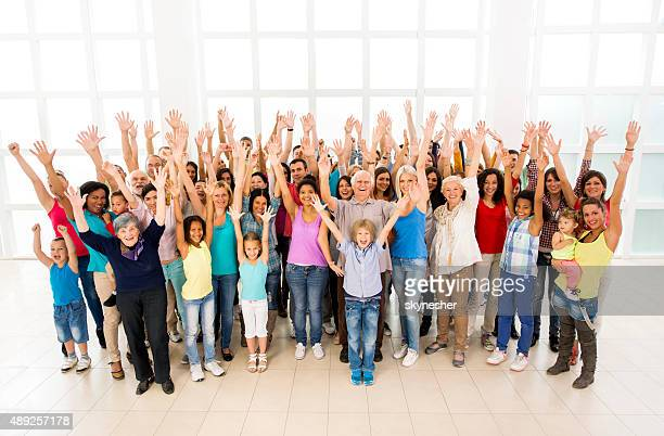 Cheerful group of people with arms raised looking at camera.