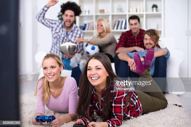 Fröhliche Gruppe junger Freunde spielen Videospiele