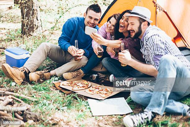 Cheerful group of young people amking selfie in the forest