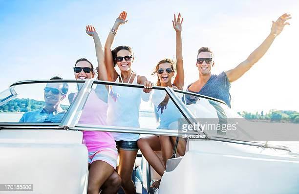 Cheerful group of young people enjoying in speedboat ride.