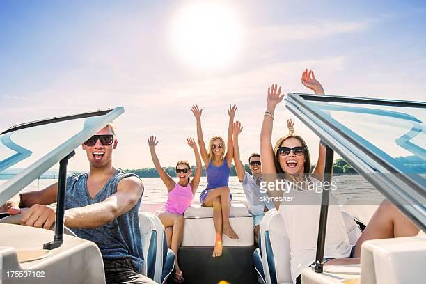 Alegre grupo de jóvenes disfrutar de paseo en bote.