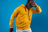 Take my picture. Waist up portrait of young man in stylish yellow sweatshirt posing on blue background. He is keeping hand near face and smiling. Isolated on blue background