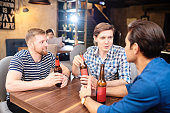 Cheerful positive young guys in casual clothing sitting at wooden table drinking beer in pub