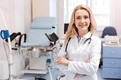 Full of joyful emotions at work. Positive delighted qualified gynecologist standing in the gynecology cabinet while expressing positivity and enjoying working responsibilities