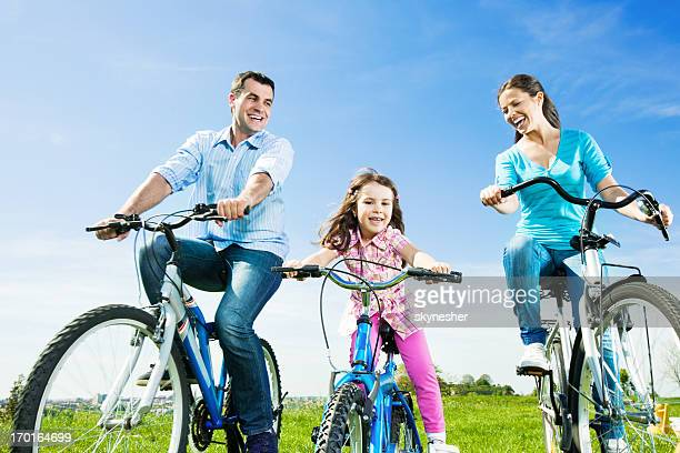Cheerful happy family riding bicycles in the park.