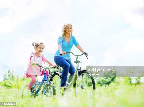 Cheerful happy mother and daughter riding bicycles in  park.