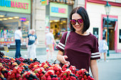 Cheerful happy young woman buying berries on a street market