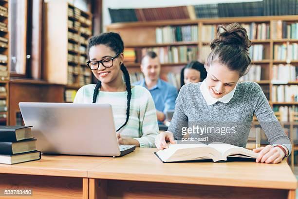 Alegre estudiantes de secundaria haciendo los deberes en la biblioteca