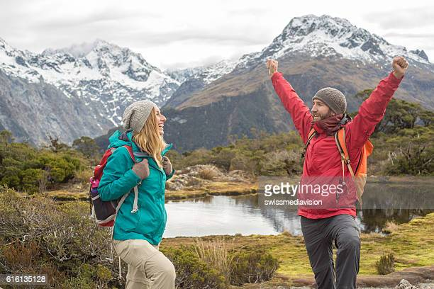 Cheerful hikers arms outstretched on mountain trail