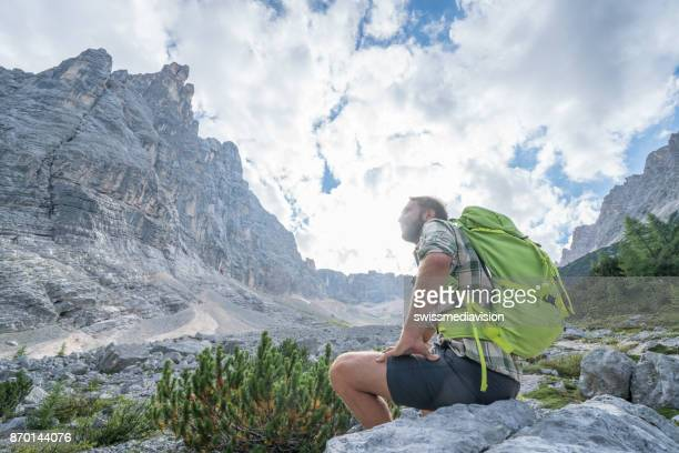 Cheerful hiking man contemplating the Dolomites in Italy