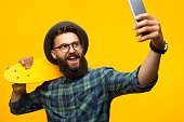 Young bearded man in glasses and hat posing with yellow skate and taking selfie with smartphone.