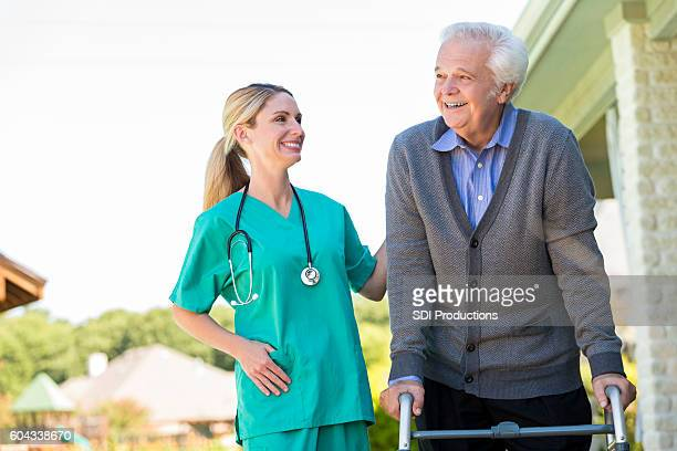 Cheerful home healthcare nurse helps patient walk outdoors
