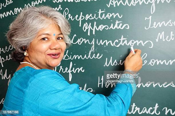Cheerful Indian Asian Woman English Teacher in Classroom with greenboard
