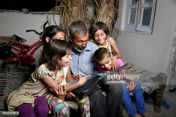 Cheerful Indian Family Holding Laptop at Home
