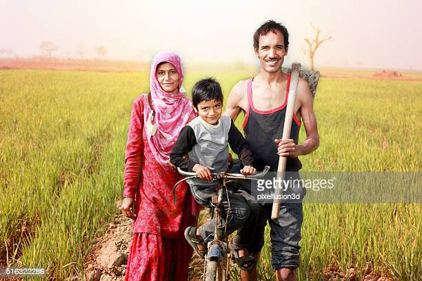 Cheerful Indian family standing in the field with bicycle