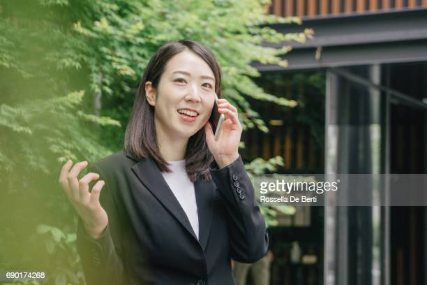 Cheerful Japanese business woman with smartphone