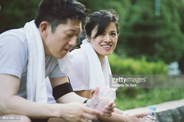 Cheerful Japanese couple relaxing after workout in a park