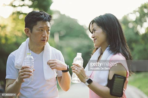 Cheerful Japanese friends relaxing outdoors in a park after workout