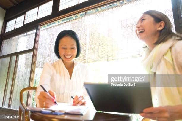Allegro giapponese donna avendo una riunione in una casa del tè