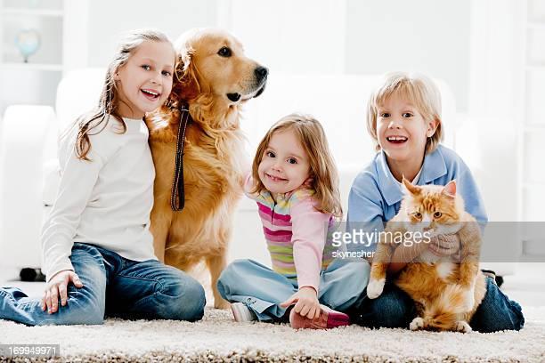 Joyeux enfants et leurs animaux domestiques à la maison.