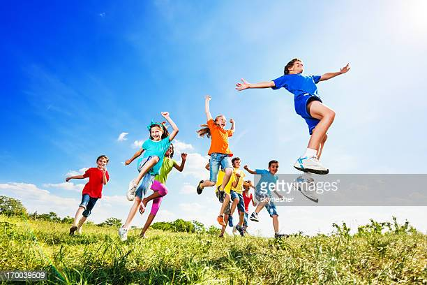 Cheerful kids jumping in field against the sky.