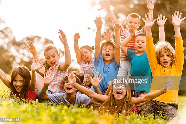 Cheerful kids screaming with raised arms at sunset.