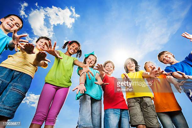 Cheerful kids with open arms looking at camera.