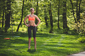 Smiling lady is standing on toes and holding hands on waist on green lawn. She is enjoying exercising in beautiful countryside. Copy space in right side