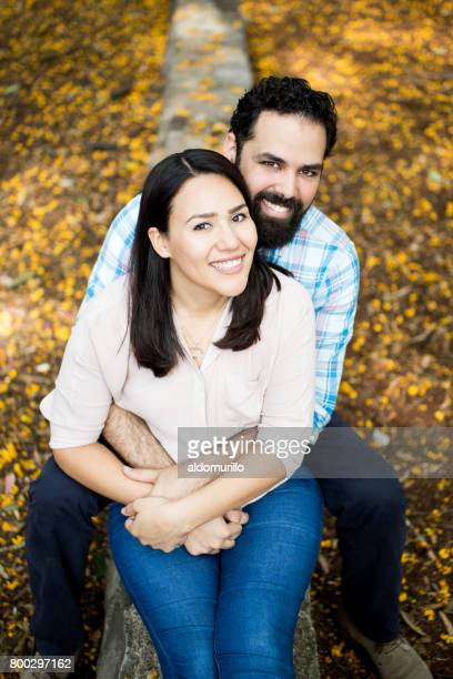 Cheerful latin couple sitting and smiling at camera