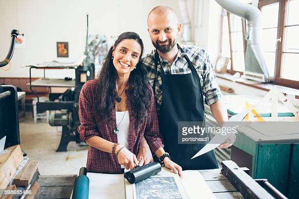 Cheerful lithography couple creating new pattern at printing house