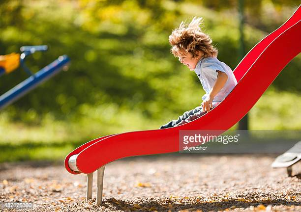 Cheerful little boy having fun while sliding outdoors.