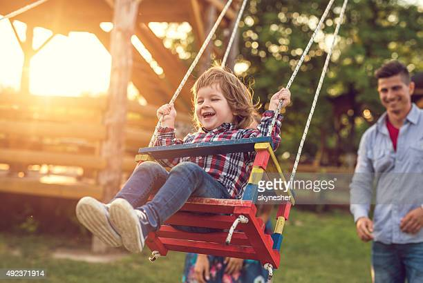 Cheerful little boy swinging at sunset.