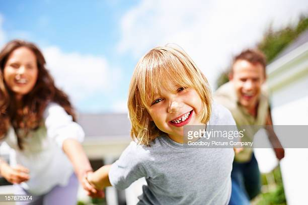Cheerful little boy with his parents having fun