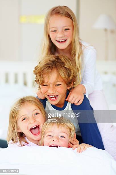 Cheerful little brothers and sisters having fun in bed