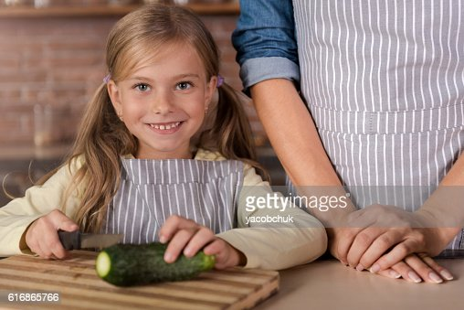 Cheerful little girl cutting a cucumber in the kitchen : Stock Photo