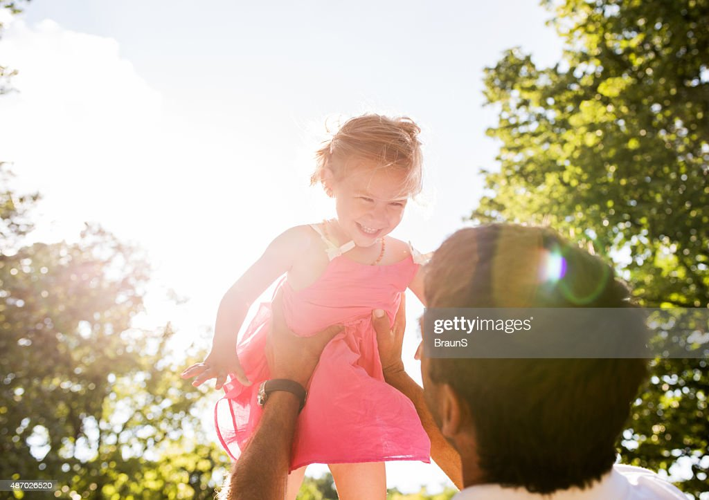 Cheerful little girl having fun with her father outdoors.