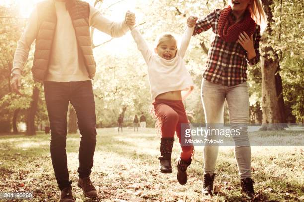 Cheerful little girl playing with parents and enjoying together in park on sunny day.
