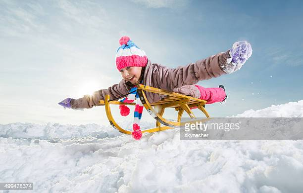 Cheerful little girl sledding and having fun on snow.