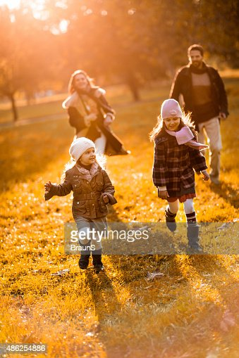 Cheerful little girls being chased by their parents in nature.