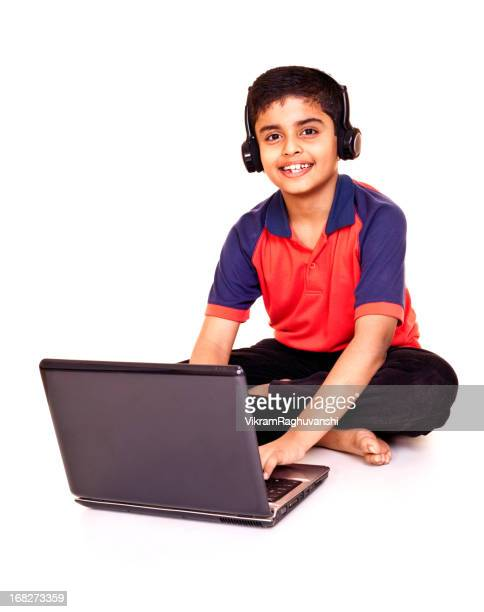 Cheerful Little Indian Boy Using Laptop Isolated on White Background