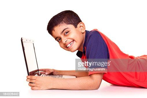 陽気なインドの少年ノートパソコンを使う白背景