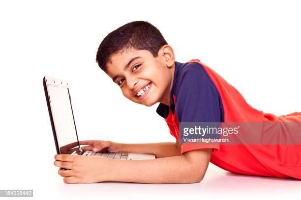 Niño Alegre Little india usando ordenador portátil aislado sobre fondo blanco
