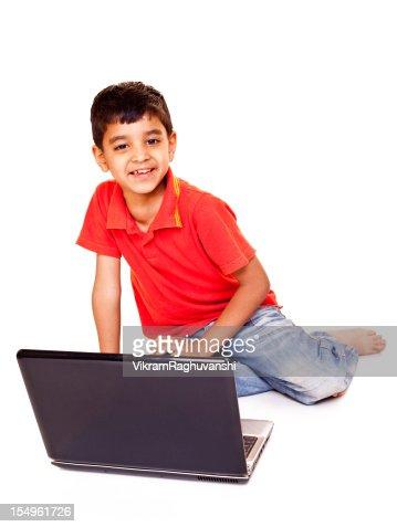 陽気なインドの少年ノートパソコンを使用して、白で分離