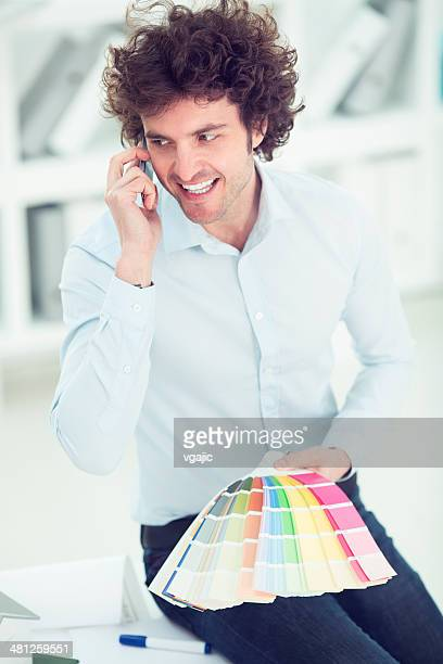 Cheerful male architect on the phone in the office.