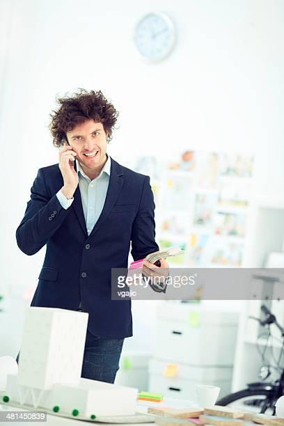 Joyeux architecte mâle sur le téléphone au bureau.