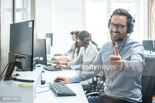 Operador de servicio de cliente masculino alegre mostrando los pulgares para arriba en oficina. : Foto de stock
