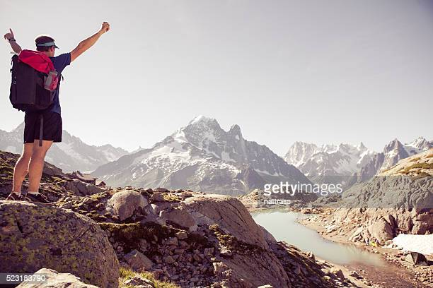 Cheerful male mountain top arms stretched out